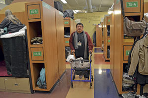 Samantha Weigel/Daily Journal Al Thaddus walks down an aisle of bunk beds where residents sleep and keep their belongings at the Safe Harbor Shelter in South San Francisco.